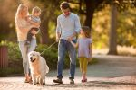 Young family taking their dog for a walk during spring day at the park.