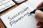 Man is writing succession planning in the book.